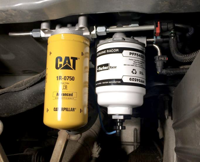 Yellow CAT fuel filter and white factory fuel/water separator installed in engine.