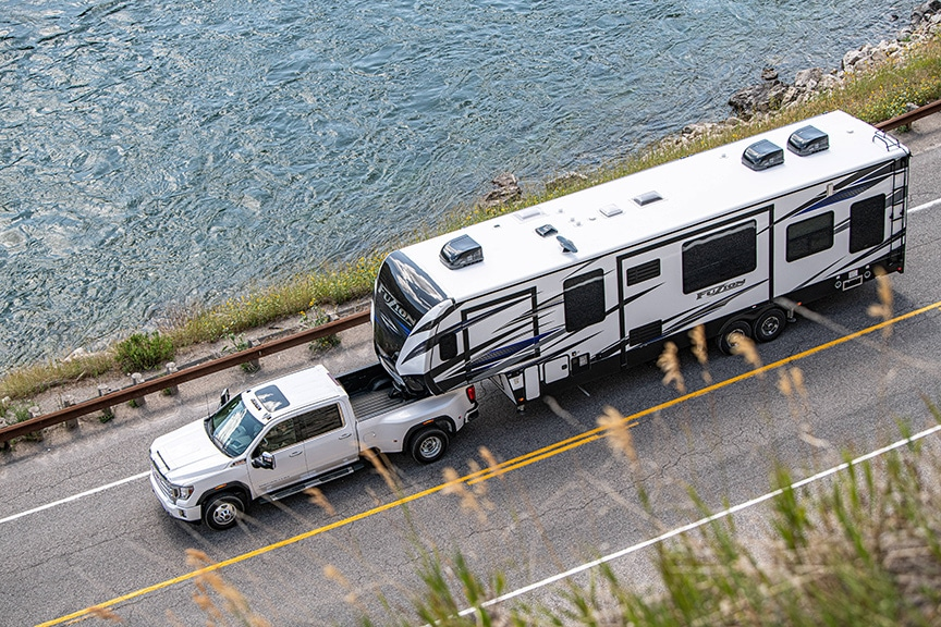 Aerial view of white Sierra truck towing a Fuzion fifth-wheel