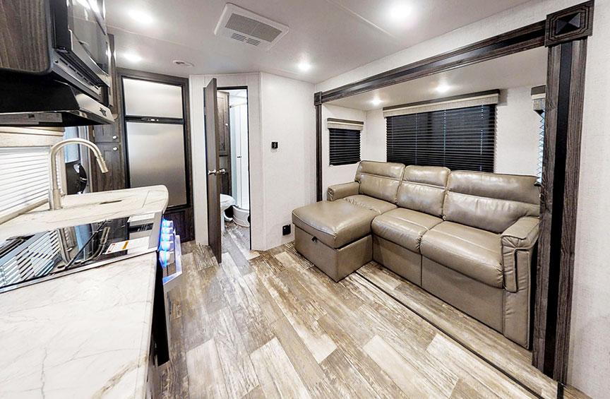 Interior of Super Lite 212FB showing L-shaped sofa and gray vinyl plank floor