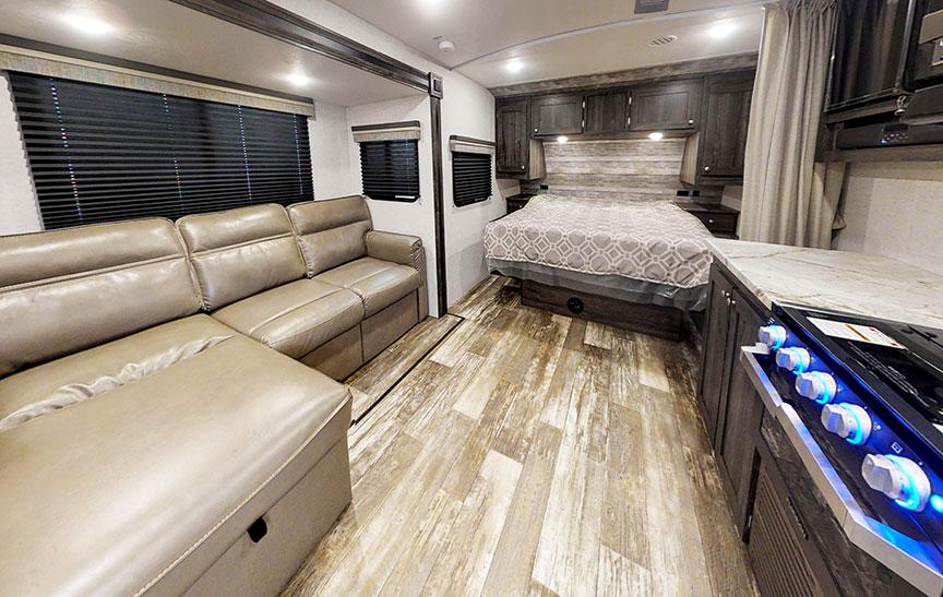 Interior of Super Lite 212FB showing queen bed and gray vinyl plank floor