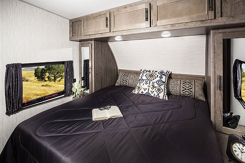 Trailer bedroom with dark bedspread on queen bed and cabinets above