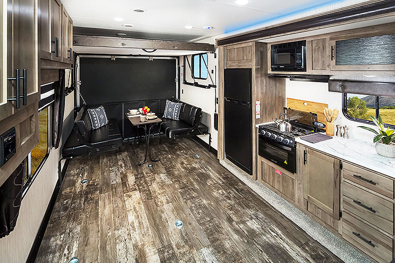 View of toy hauler from midship to rear with plank-look flooring, kitchen and rear sofas.