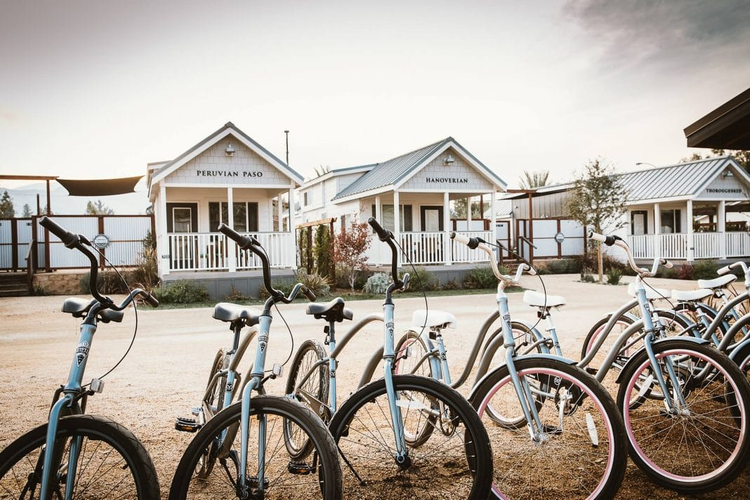 Light blue bicycles parked in front of white cabins on dirt road