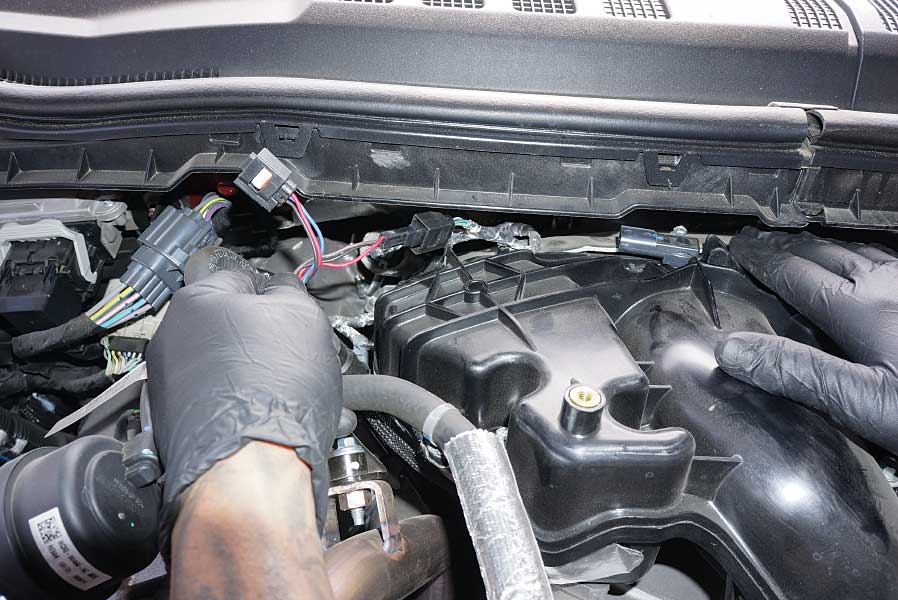 Technician plugs the Derringer harness into the sensor and OEM harness