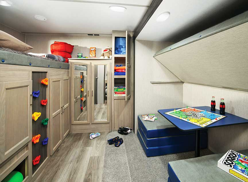Rear bunk room in 326BHDS trailer with a climbing wall up to the top bunk.