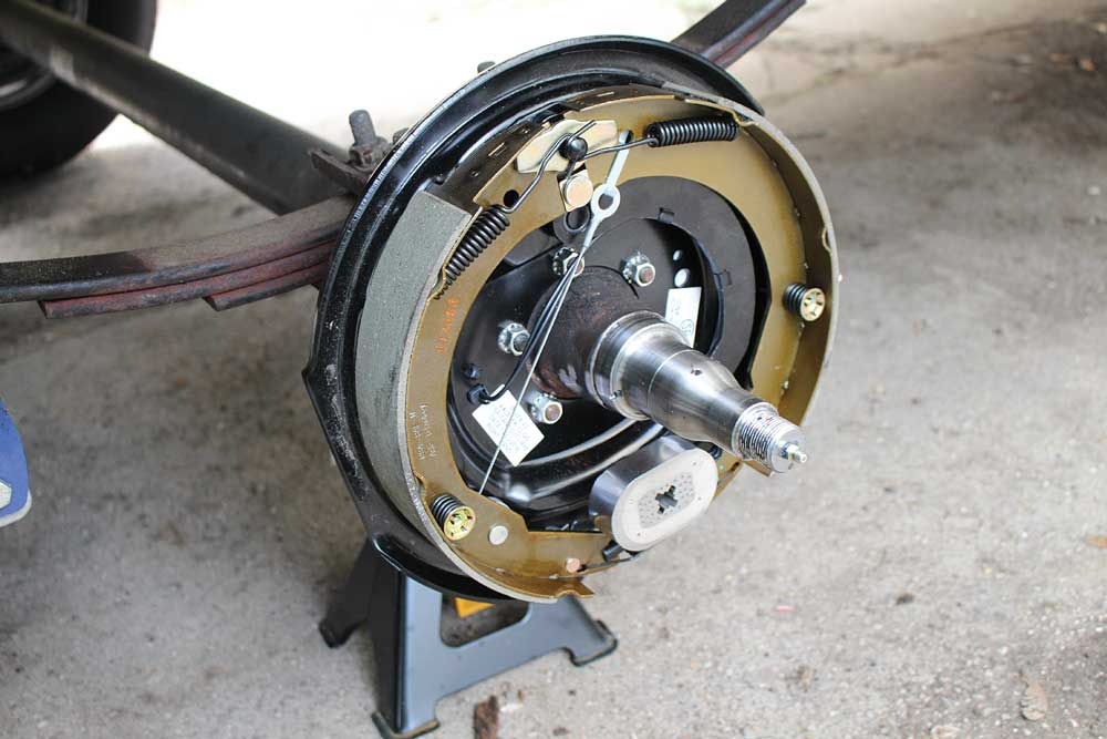 Five backing-plate nuts and washers attach the brake assembly to the axle housing.