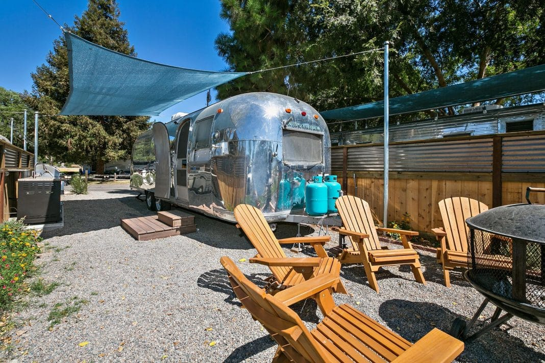Silver Airstream parked in nice campground with wooden chairs