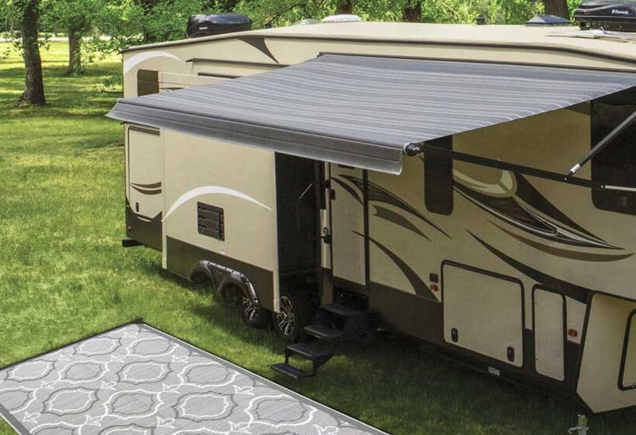 Gray patio mat next to fifth-wheel trailer with awning extended.