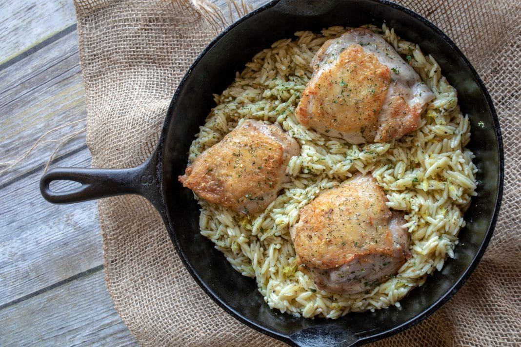 Cast iron skillet with chicken and orzo
