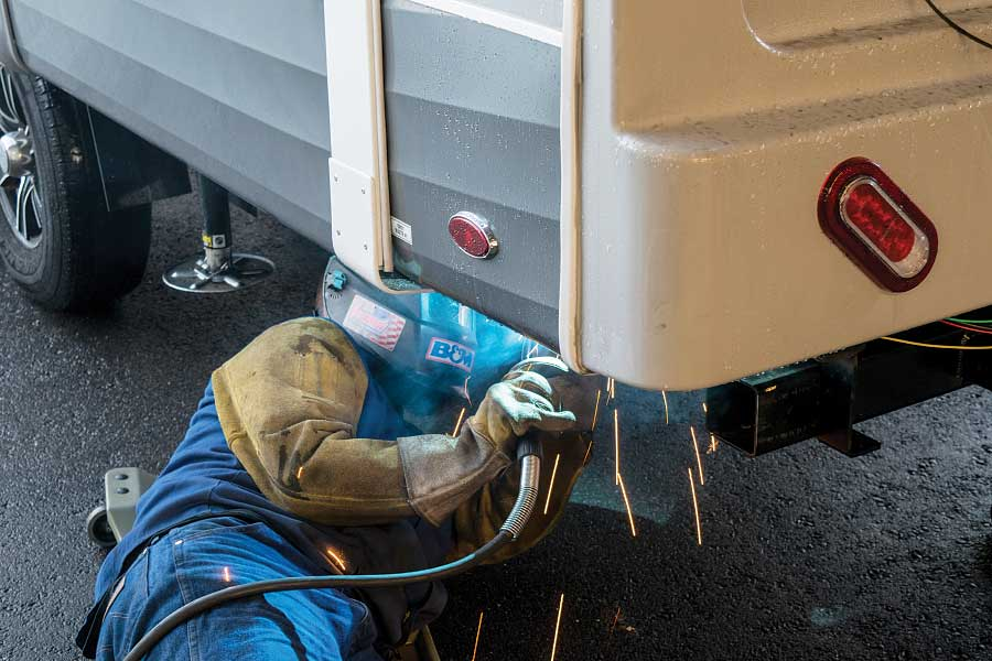 A welding techinician attaches the mounting kit to the frame of a customer's fifth-wheel trailer.