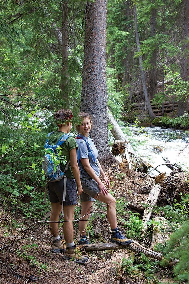 Sophia Clark and Nicole Robertson pause by Difficult Creek during a hike in the Collegiate Peaks Wilderness near Difficult Campground.