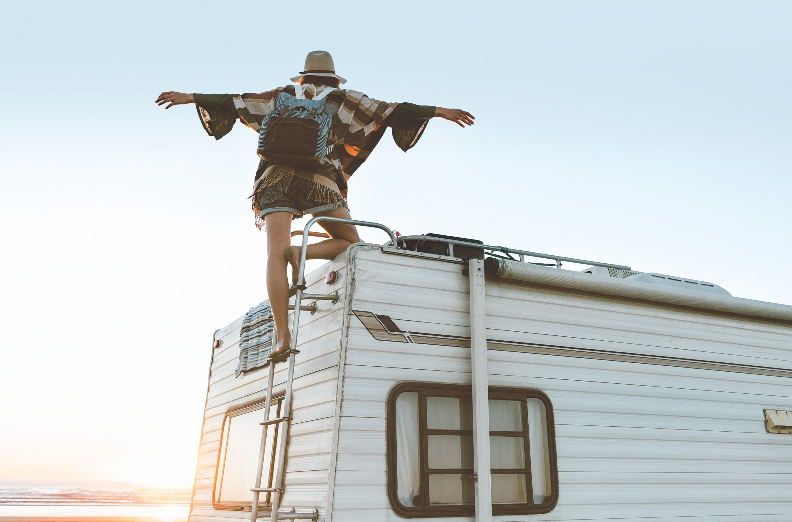 Charming girl with hat, poncho, backpack standing on roof of recreational vehicle on the ocean beach at sunset.