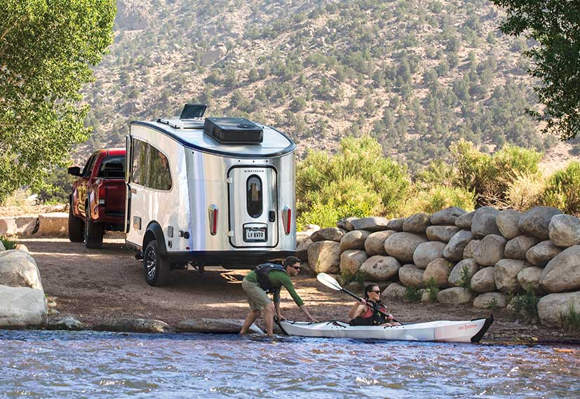 Silver Airstream Basecamp trailer with kayak in foreground.