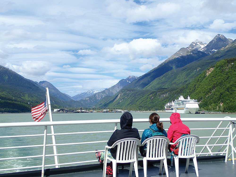 Three people sitting on ferry with cruise ship in sight
