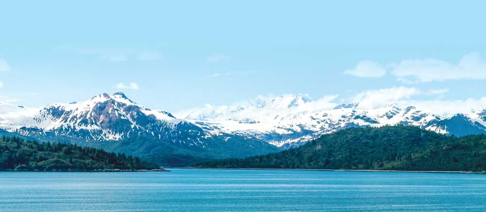 spectacular views of snowcapped mountains and pine trees over water