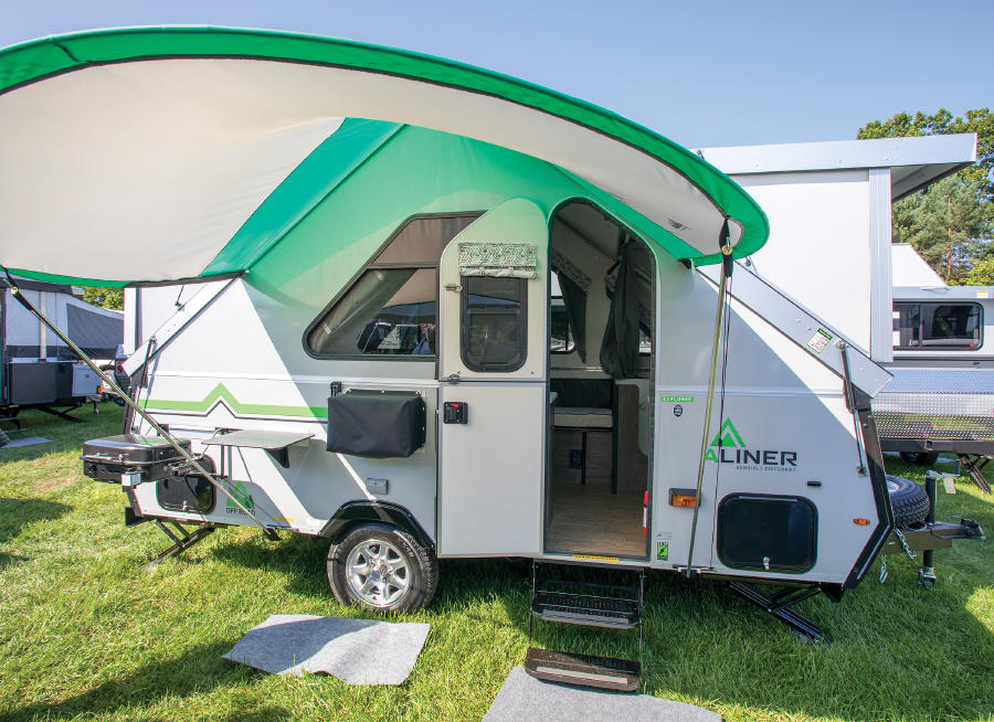 Small travel trailer with curved green and white awning parked