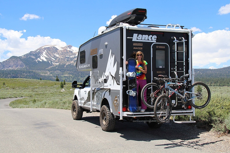 Author Donya Carlson holding snowboard on back of Lance Altimeter with bikes on rack.