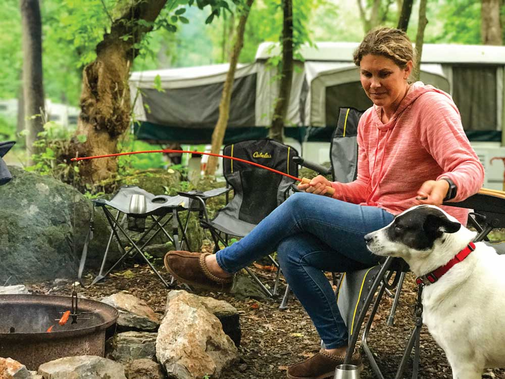 Woman holding stick over campfire looking at dog with trailer in background