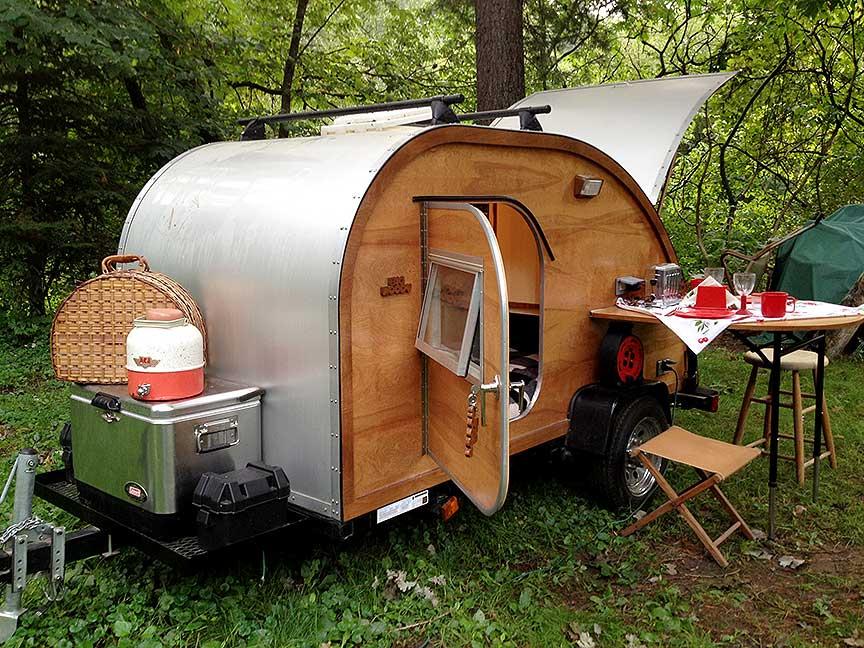 Wood-sided Big Woody teardrop trailer with rear kitchen open.
