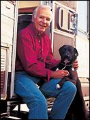 Older man wearing red shirt sitting in RV with black dog