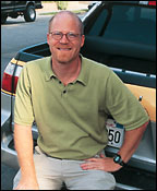 Man wearing green shirt and glasses sitting against truck bumper