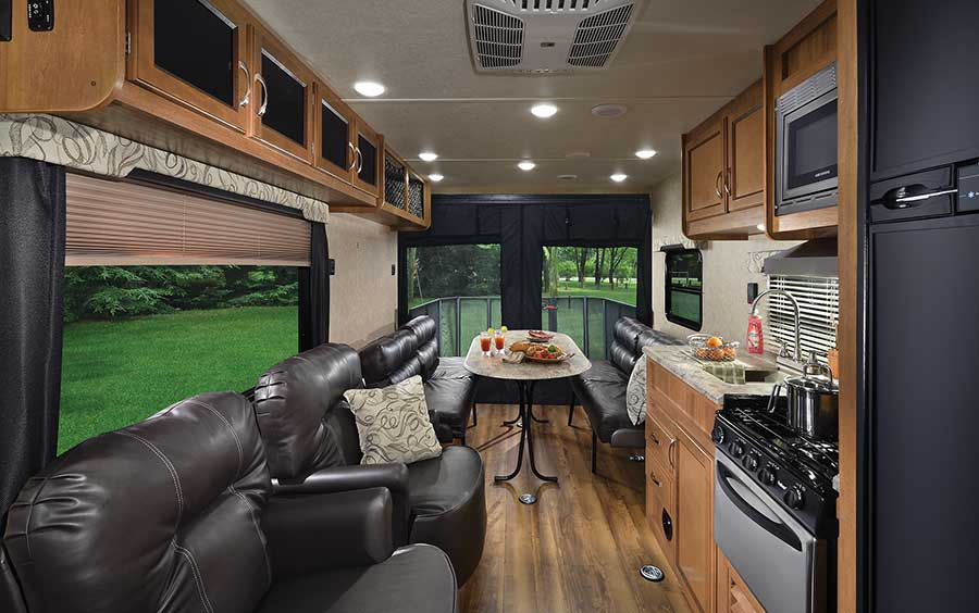 In minutes, the 26TH's rear dining area with a removable table turns into wall-to-wall sleeping space or a completely open garage with 12 tie-downs. The rear screen wall is standard.