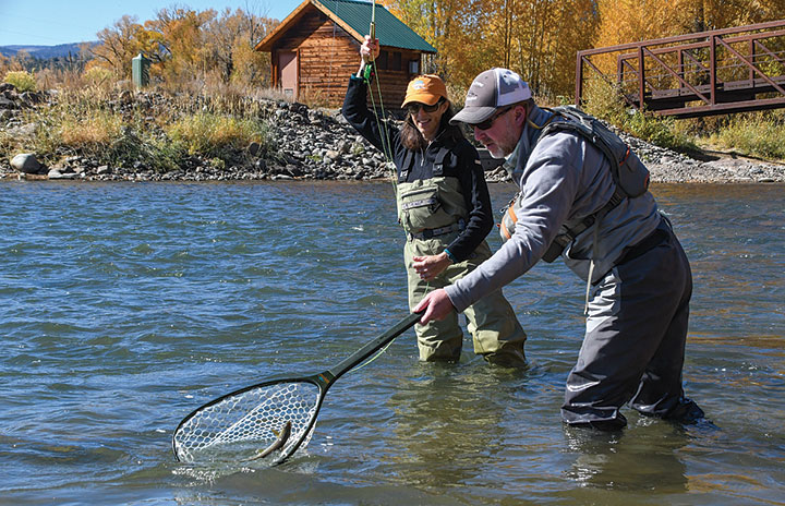 Two fisherman up to knees in Upper Rio Grande River netting a brown trout
