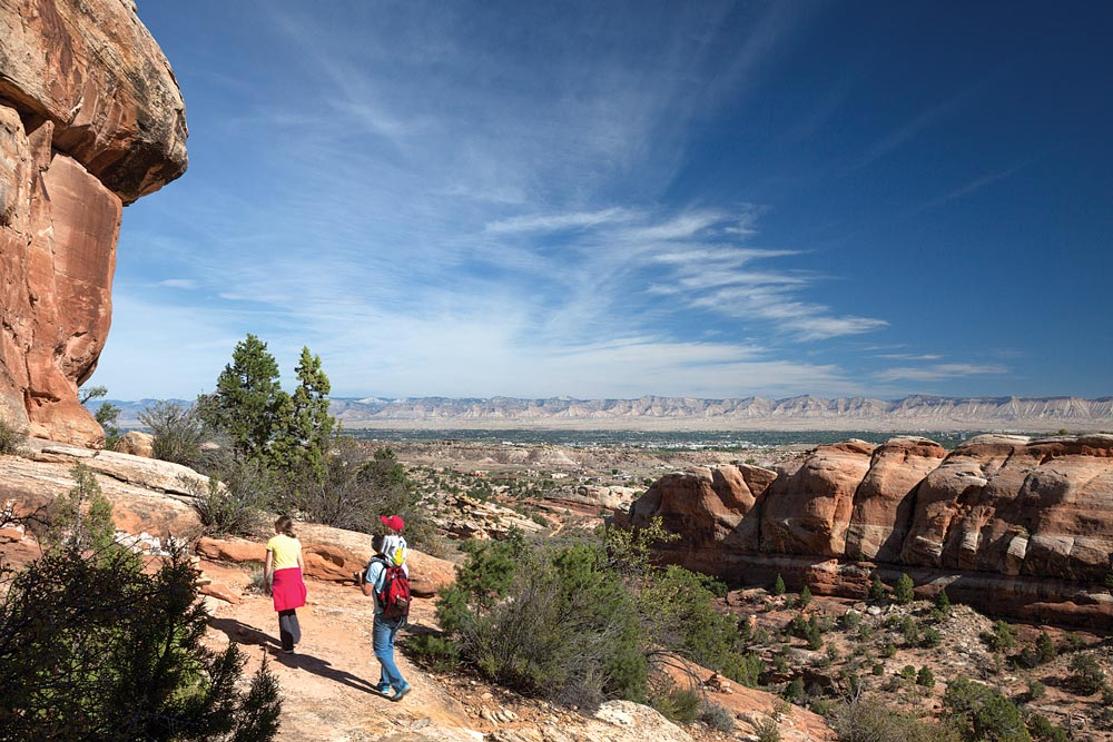 A family hikes to the natural rock room called the Devils Kitchen. In the distance is the town of Grand Junction, located in Colorado's wine country.