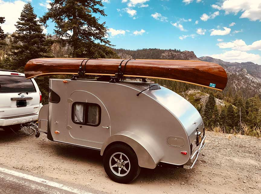 Silver Camp-Inn trailer on road with canoe on top rack.