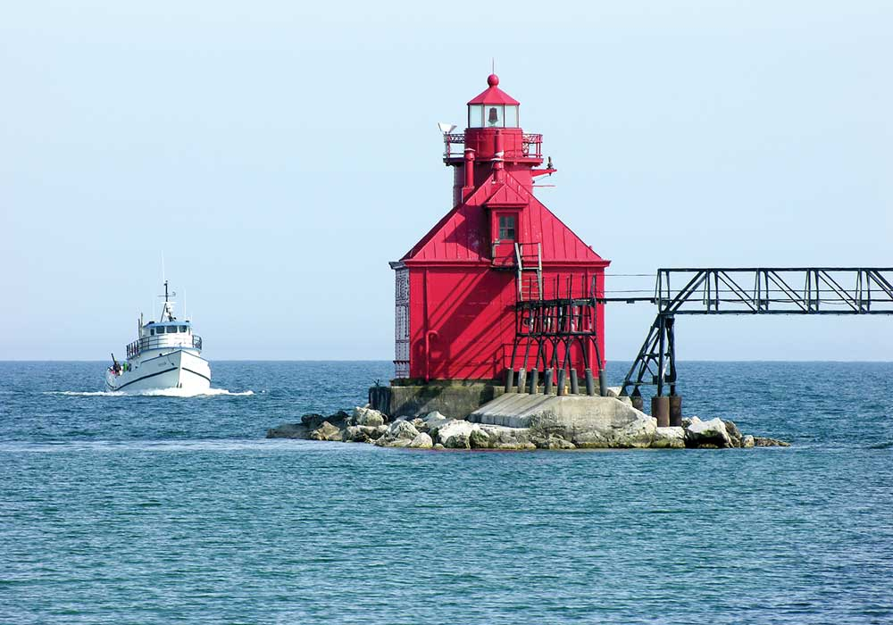 The red Sturgeon Bay Canal North Pierhead Light welcomes mariners at the Lake Michigan entrance to the Sturgeon Bay Ship Canal just outside the city of Sturgeon Bay.