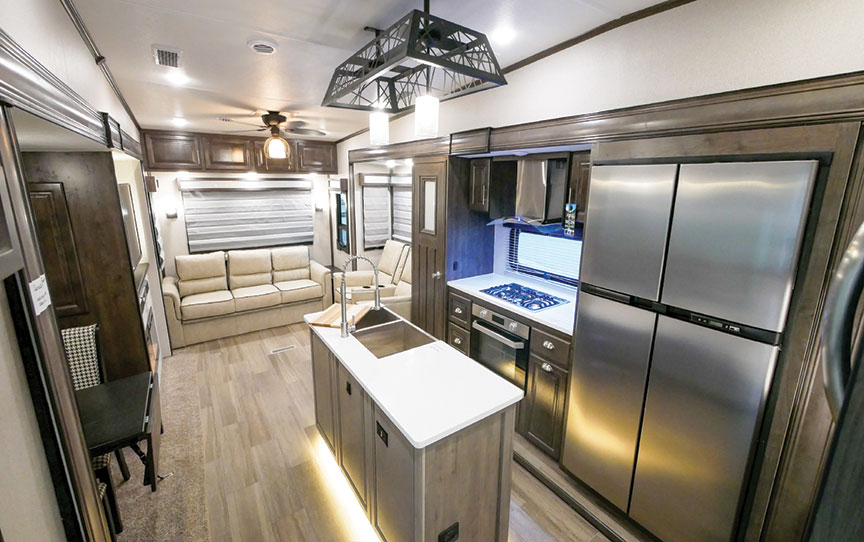 Living area and kitchen island of Cardinal Luxury 345RLX fifth-wheel