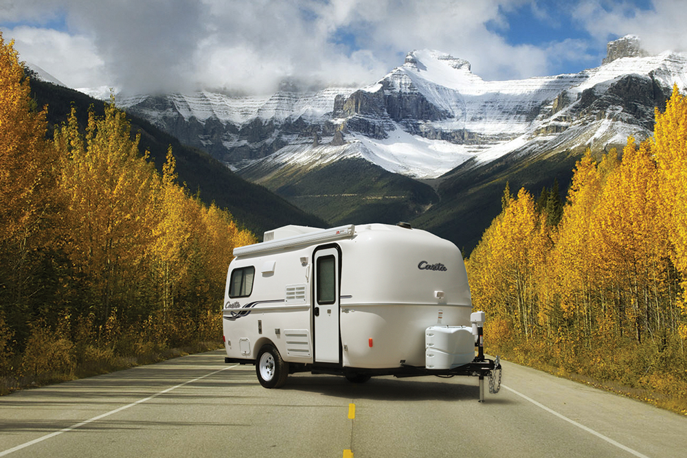 White Casita Spirit Deluxe parked in middle of highway with gorgeous snowy mountains and golden trees