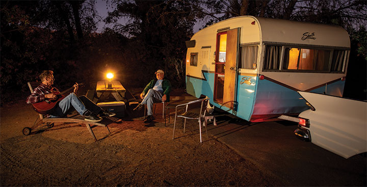 Nighttime photo with lantern on picnic table with 1959 Shasta Airflyte