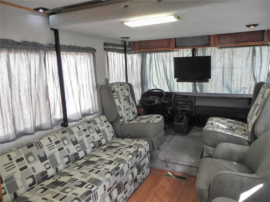 The Electromajic bed is stored in the ceiling of the living area above the sofa and chairs.