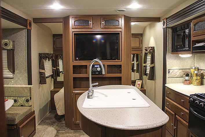 The island galley counter has a twin-basin sink and a high-rise faucet.