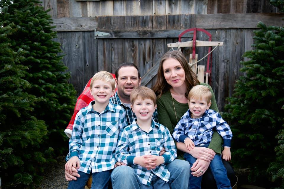 Family of five smiling at camera, kids wearing matching blue checkered shirts