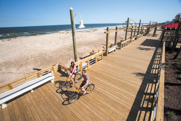 A couple enjoys a leisurely bicycle ride on the Carolina Beach boardwalk.