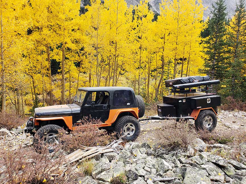 Orange Jeep towing Crawlorado trailer with aspen trees in background.