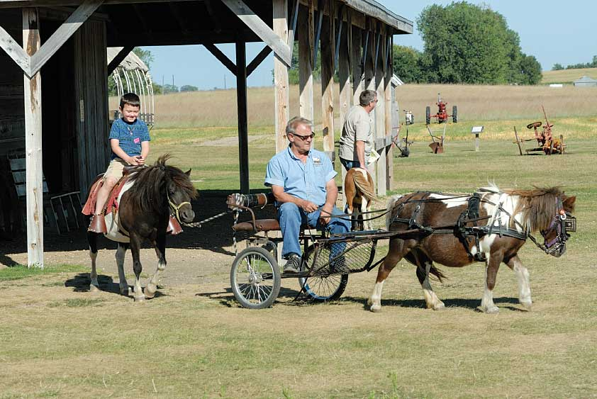 A guide at Ingalls Homestead just outside of De Smet, South Dakota, uses a pony-driven cart to take a young tourist for a pony ride.