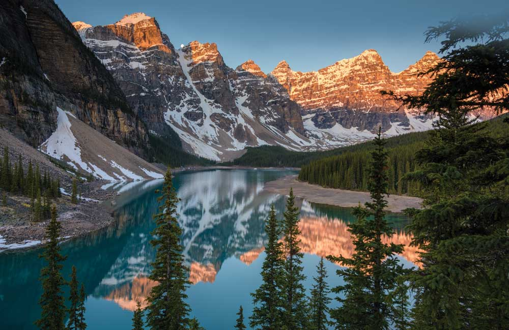 Moraine Lake, in the Valley of the Ten Peaks glowing pink in sunrise light
