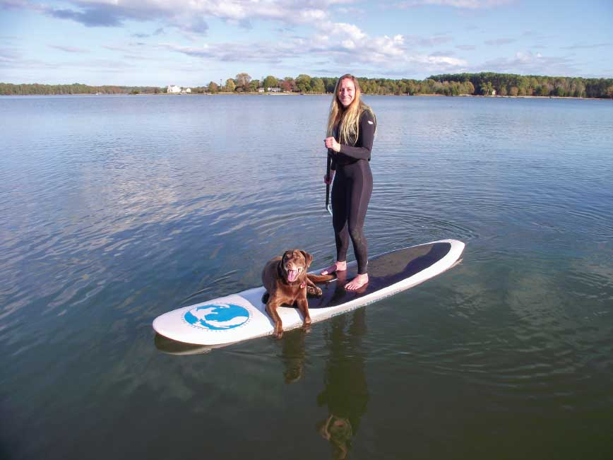 An all-around fiberglass board has enough volume to float a paddler and her pet.