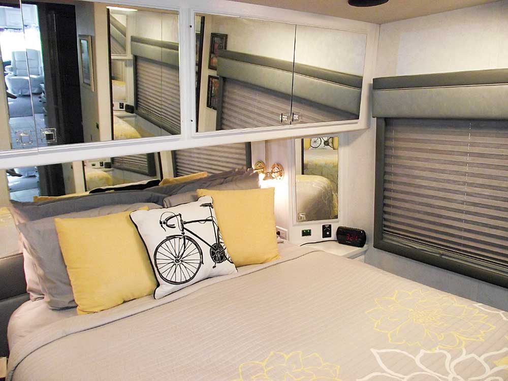 The rear bedroom features mirrored cabinet doors and a roomy queen-size bed.