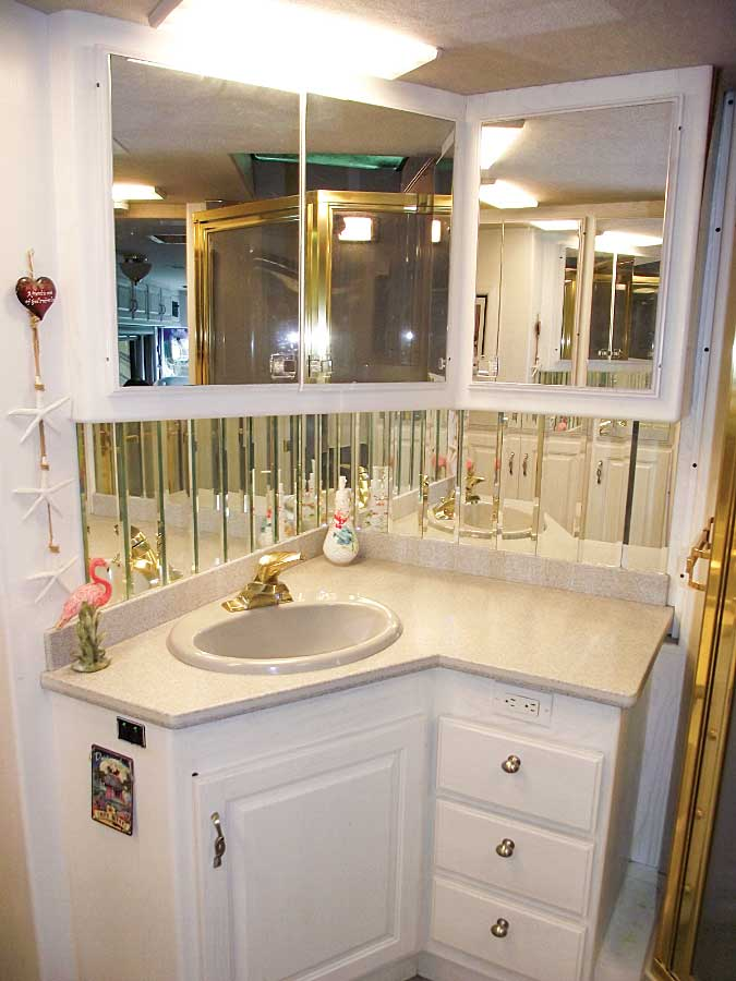 The mirrored backsplash and an emphasis on white gives a sense of space in the bathroom.