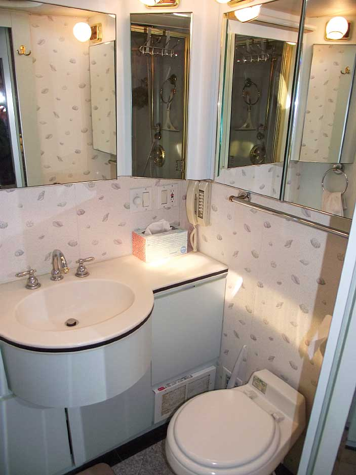 The curved vanity and mirrored cabinets help open up space in the bathroom.