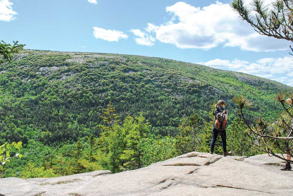 A hiker peers out from the top of South Bubble Mountain.