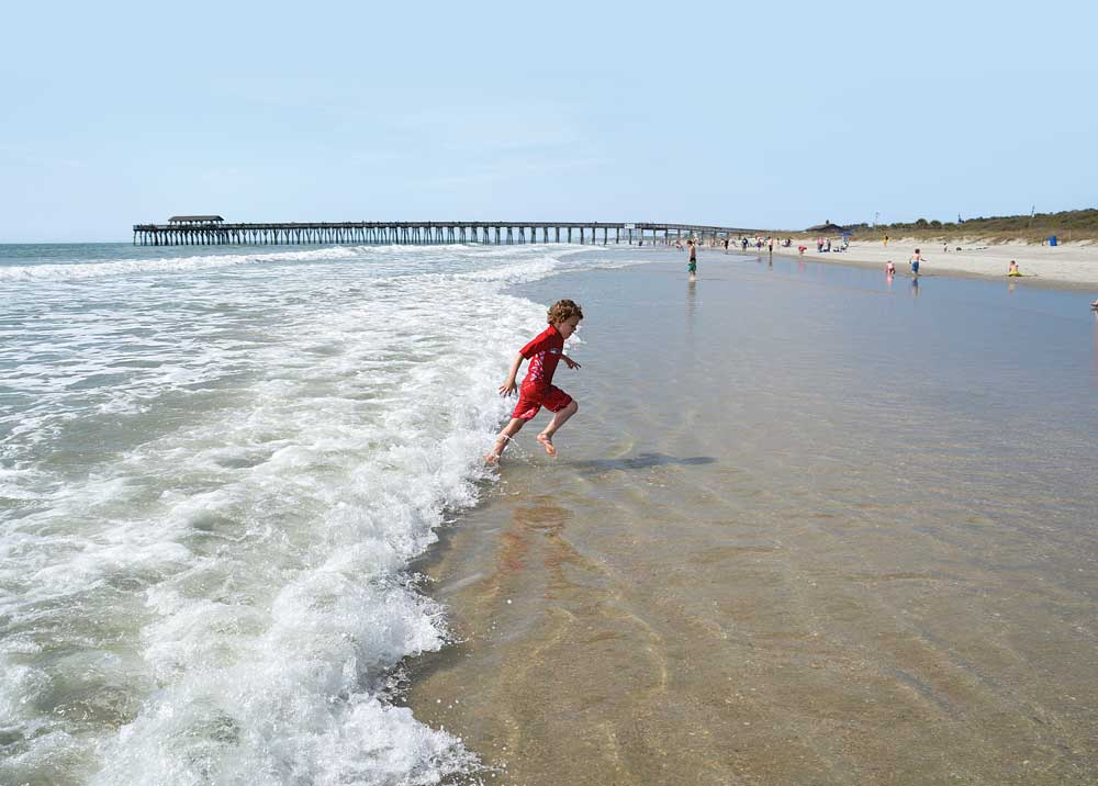 Myrtle Beach State Park, young boy in red swim suit running in water