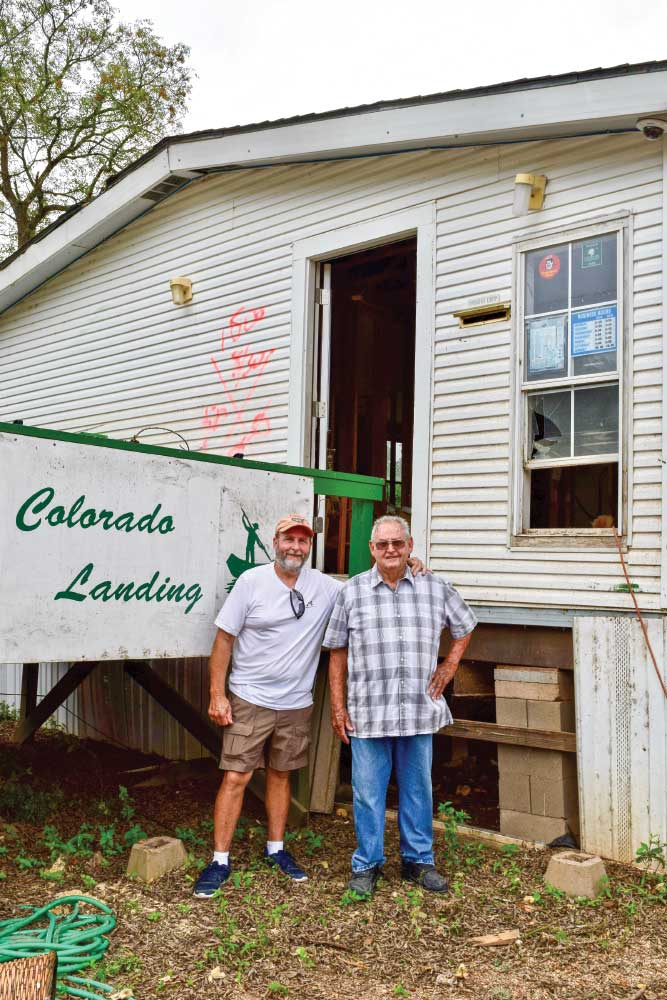 Two older men standing in front of Colorado Landing sign and worn building