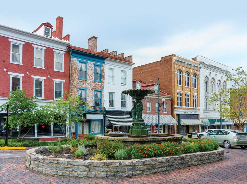 Colorful buildings stand side by side along historic brick roads, and a fountain is the centerpiece of Market Street.