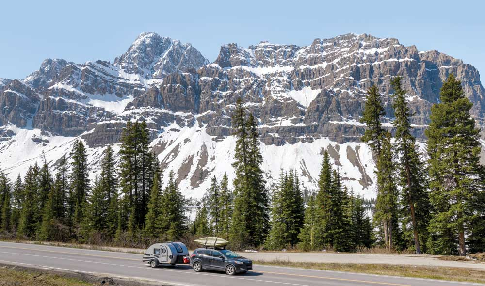 A car and teardrop trailer on the Icefields Parkway in the Canadian Rockies