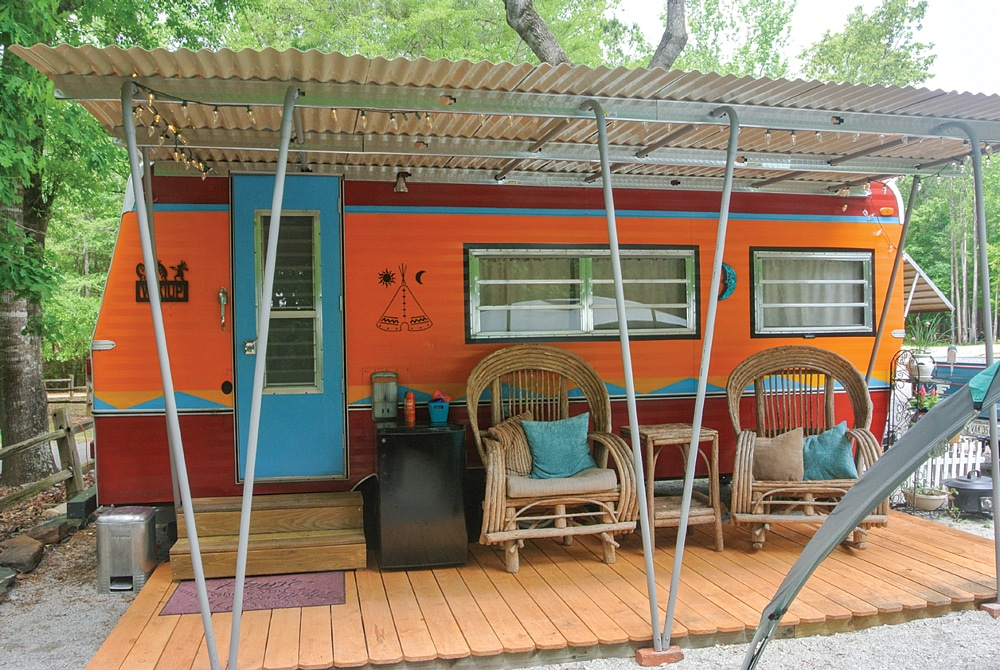 Orange and blue vintage trailer with porch, surrounded by beautiful landscape.